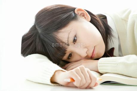 机に伏せて考え事をする女子高校生の写真素材 [FYI02070931]