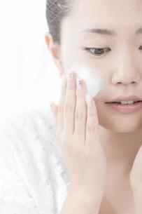 洗顔料で顔を洗う女性の写真素材 [FYI02070975]