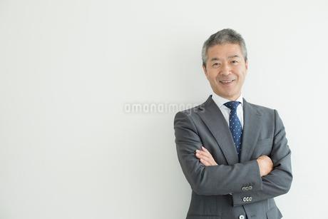 壁を背に立つミドルビジネスマンの写真素材 [FYI02070998]