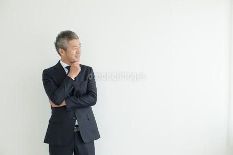 壁を背に立つミドルビジネスマンの写真素材 [FYI02071018]
