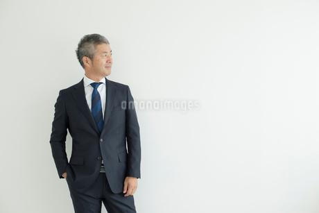 壁を背に立つミドルビジネスマンの写真素材 [FYI02071093]