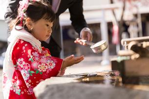 手水場で手を洗う七五三和装の女の子の写真素材 [FYI02071096]