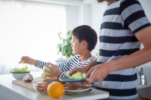 料理をする男の子と父親の写真素材 [FYI02071115]