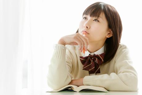 ノートを取りながら考える女子高校生の写真素材 [FYI02071202]