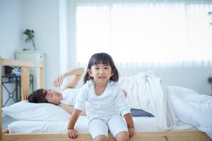 ベッドに腰掛ける女の子と目覚める母親の写真素材 [FYI02071210]