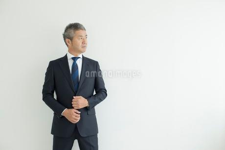 壁を背に立つミドルビジネスマンの写真素材 [FYI02071249]