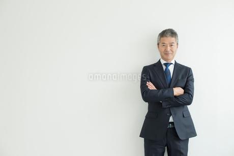 壁を背に立つミドルビジネスマンの写真素材 [FYI02071293]