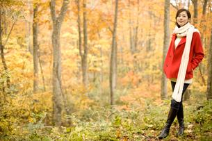 紅葉の森林と赤いコートと白いマフラーを着た女性の写真素材 [FYI02071316]