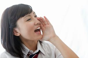 口に手を当て叫ぶ女子高校生の写真素材 [FYI02071331]