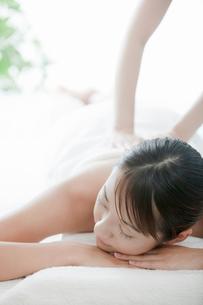 うつ伏せで背中をマッサージされている若い女性の写真素材 [FYI02071332]