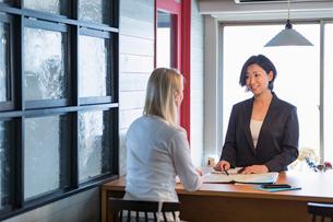 外国人女性と話す旅行代理店の日本人スタッフの写真素材 [FYI02071353]