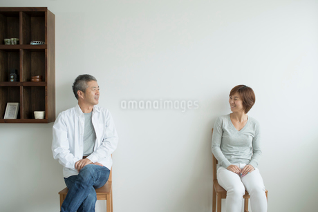 壁を背に椅子に座るミドル夫婦の写真素材 [FYI02071357]