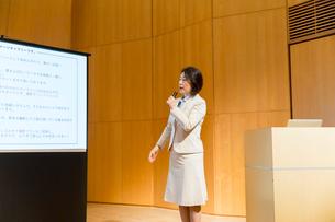 スクリーンの前でマイクを持って話すスーツ姿のミドル女性の写真素材 [FYI02071362]