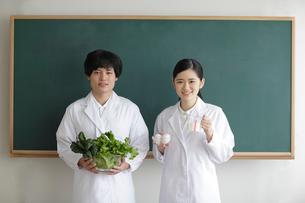 黒板の前に立つ栄養士2人の写真素材 [FYI02071372]