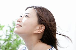 風を受けて微笑む若い女性の写真素材 [FYI02071375]