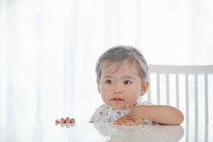 テーブルに腰掛ける女の子の写真素材 [FYI02071528]