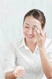 化粧落としで目元を拭く若い女性の写真素材 [FYI02071558]