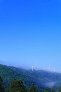 風車と朝霧の山並みの写真素材 [FYI02089786]