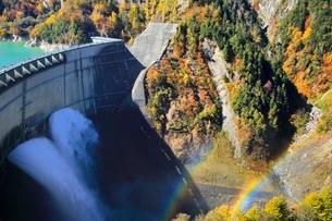 紅葉の黒部ダムと放水に虹の写真素材 [FYI02098243]
