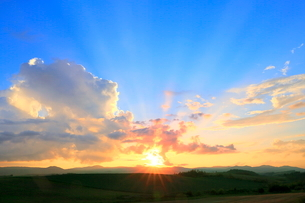 入道雲と夕日に光芒の写真素材 [FYI02098387]