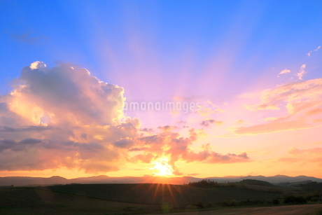 入道雲と夕日に光芒の写真素材 [FYI02098435]