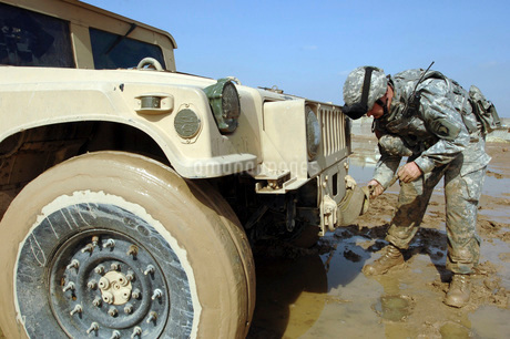 Soldier unties a rope to tow a humvee out of the mud.の写真素材 [FYI02098704]