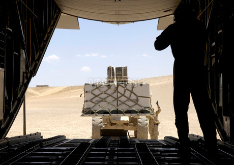 A forklift loads cargo onto a C-130 Hercules.の写真素材 [FYI02098827]