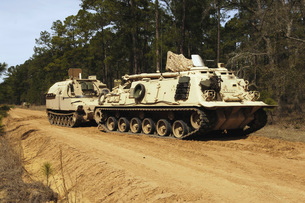 An M-88 recovery vehicle begins to tow an M992 field artilleの写真素材 [FYI02098864]