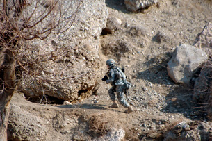 U.S. Army soldier walks up the side of a hill to look at cavの写真素材 [FYI02099191]