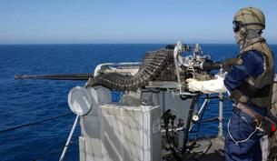 A U.S. Navy Gunner's Mate firing a .50-caliber machine gun dの写真素材 [FYI02099332]