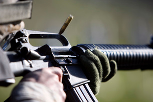 A round flies from the chamber of an M-16A2 service rifle.の写真素材 [FYI02099608]