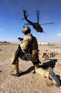A soldier conducts security for an HH-60 Pavehawk helicopterの写真素材 [FYI02099932]
