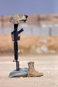 Boots, rifle, dog tags, and protective helmet stand in solitの写真素材 [FYI02100436]