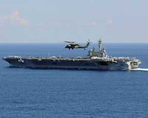 An MH-60S Seahawk helicopter flies over USS George H.W. Bushの写真素材 [FYI02100644]
