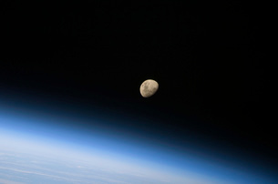 A gibbous moon visible above Earth's atmosphere.の写真素材 [FYI02100816]