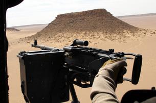 A UH-60 Blackhawk crew chief holds an M240G medium machine gの写真素材 [FYI02100886]