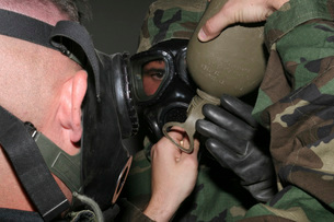 A solder assists a Marine in helping him fit his gas mask'sの写真素材 [FYI02101004]