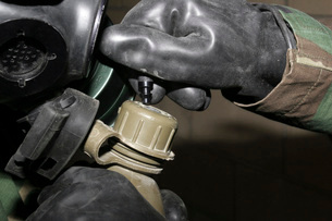 A Marine inserts a drinking tube into his canteen.の写真素材 [FYI02101370]
