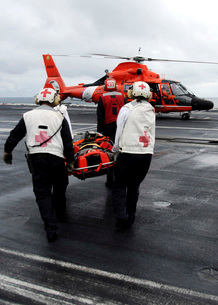 Personnel carry an injured sailor to a coast guard MH-65 Dolの写真素材 [FYI02102874]