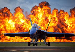 A wall of fire erupts behind a U.S. Navy F/A-18 Hornet aircrの写真素材 [FYI02102914]