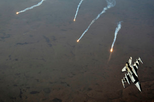 An F-16 Fighting Falcon jet pitches out while popping flaresの写真素材 [FYI02103154]