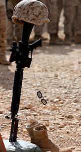 Boots, a helmet, rifle and dog tags serve as a representatioの写真素材 [FYI02103217]