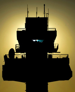 The setting sun silhouettes an air traffic control towerの写真素材 [FYI02103509]