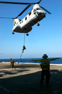 Personnel fast-rope from the rear of a CH-46E Sea Knight.の写真素材 [FYI02103575]