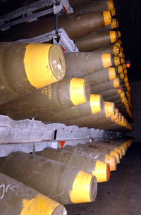 Racks of bombs sit inside the interior of a warehouse.の写真素材 [FYI02104017]