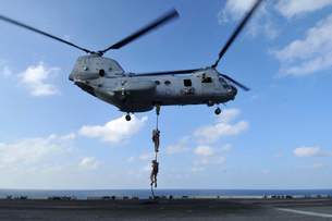 A trio of Marines fast rope from a CH-46E Sea Knight helicopの写真素材 [FYI02104181]