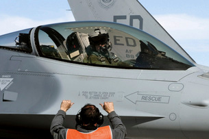 round personnel prepares to taxi an F-16 Fighting Falcon.の写真素材 [FYI02104437]