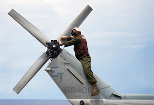 A Marine conducts maintenance on the tail of an UH-1N Huey hの写真素材 [FYI02104649]