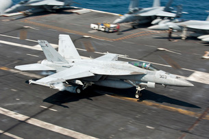 An F/A-18E Super Hornet hooks an arresting gear wire while lの写真素材 [FYI02104782]