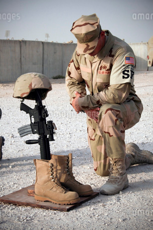 A soldier bows to pay tribute to a fallen soldier.の写真素材 [FYI02104840]